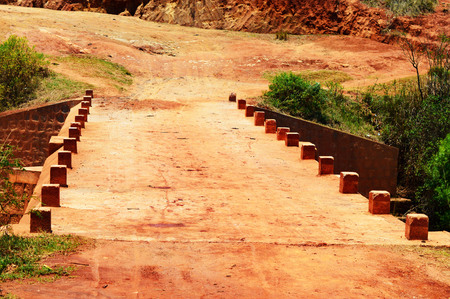 A bridge made from concrete and bricks across a small river