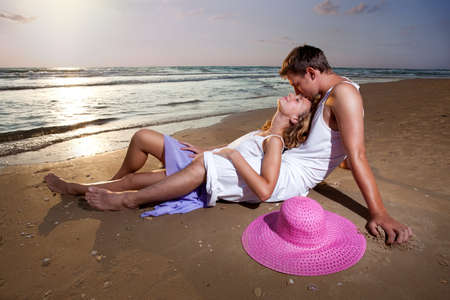 two relaxed  people lie on  sand  at sunset background photo