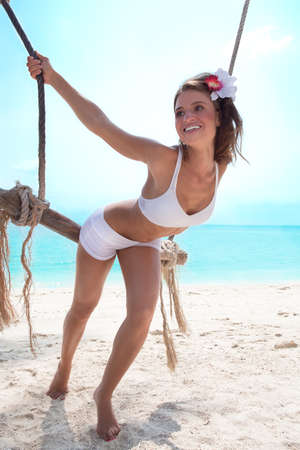 woman rope: Smiling young woman on a beach playing  with swing
