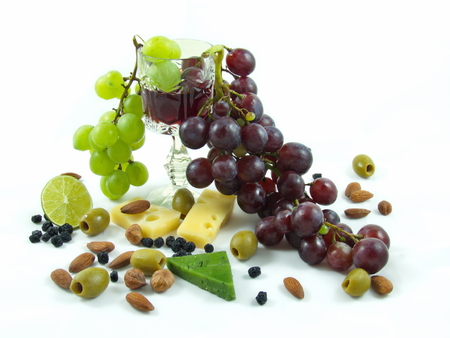 Wine, grapes, cheese, almonds, olives, hazelnuts, cranberries, limes and green cheese on a white background.