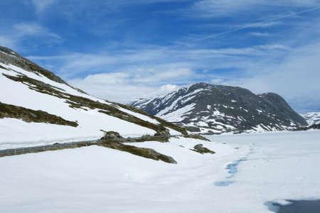 Road way along the snowing lake and rock, summer photo
