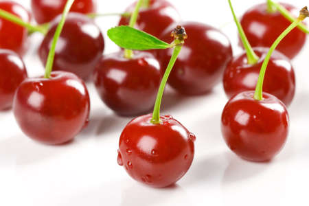 sweet juicy cherries with drops are on the white surface