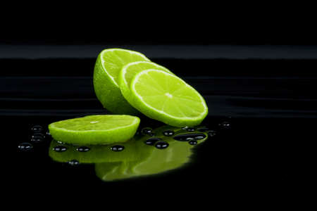 Lime on black and drops Stock Photo