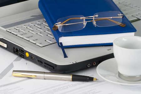 White laptop, glasses, pen, cup Stock Photo