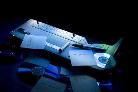 cdrom: lightening laptop and objects, diks, pen, notes, keyboard Stock Photo