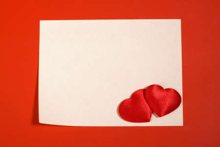 Empty sheet and two red textile hearts photo