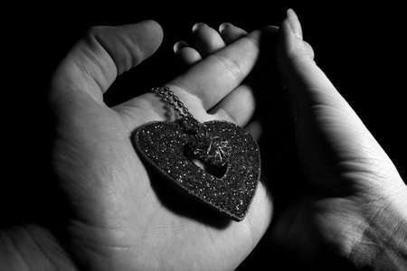 Heart with necklace in man hand like a declaration in love to woman Stock Photo - 6350223