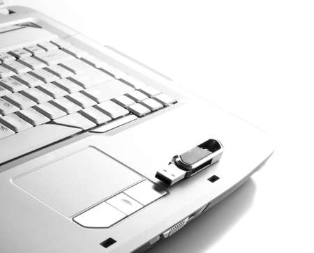 Part of white keyboard with flash device on it. Stock Photo