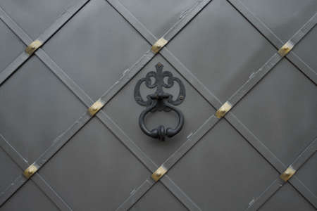 Metal gate with door handle like a knocker. photo