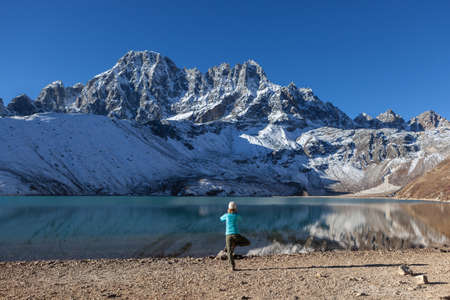 vriksasana: Young woman practicing yoga tree pose (vriksasana) on the shore of turquoise Gokyo lake under snowy mountain peaks. Himalayan mountain ridge reflecting in mirror surface of emerald green Gokyo lake.