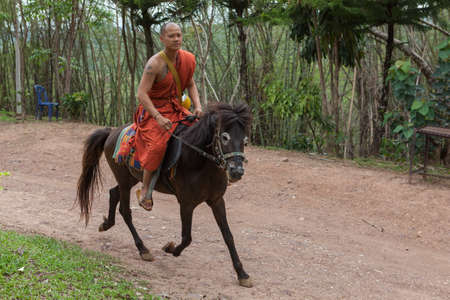 CHIANG RAI, THAILAND - May 21, 2016: Young Buddhist monk fast riding a horse in Golden Horse Temple (Wat Phra Archa Thong). Monk wearing traditional orange robe galloping a horse. Editorial