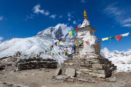 Buddhist prayer flags on a buddhist chorten on Everest Base Camp route in Himalayas, Nepal. Waving buddhist prayer flags in a beautiful mountain landscape near Dingboche village.