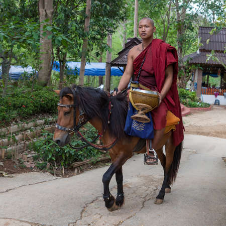 straddle: CHIANG RAI, THAILAND - May 21, 2016: Young Buddhist monk riding a horse in Golden Horse Temple (Wat Phra Archa Thong). Monk wearing traditional red robe and carrying alms bowl straddle a horse.
