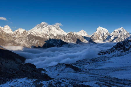 Mount Everest view from Renjo La pass. Breathtaking mountain valley filled with curly clouds. Dramatic snowy peak of Everest rise above river of clouds. Sagarmatha National Park, Nepal, Himalayas. Stock Photo