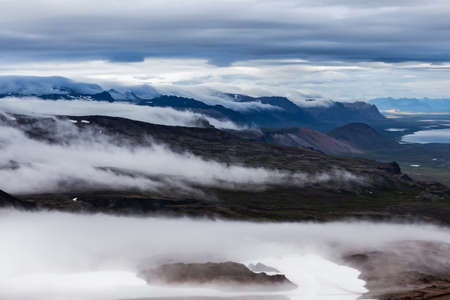 western slope: Clouds flowing low in the beautiful Iceland mountain landscape - view from the slope of Snaefellsjokull volcano. Hiking in Saefellsnes peninsula in western Iceland. Stock Photo
