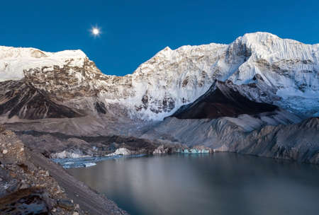 Grey moraine lake and snowy mountain peak in the moon light in Himalayas, Nepal. Mirror water of a big moraine lake. Imja Tsho moraine lake at the foot of the Imja Glacier. Stock Photo