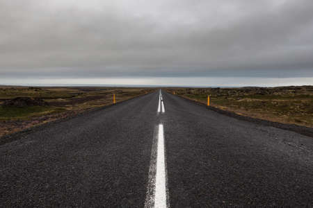 Iceland road leading straight to the horizon. Empty straight road line in rural Icelandic landscape on a cloudy summer day. Road on Saefellsnes peninsula in western Iceland. Imagens