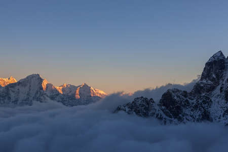 Picturesque mountain valley filled with curly clouds during sunset. Dramatic snowy peaks rise above river of clouds and lit up by magical orange sun light. Sagarmatha National Park, Nepal, Himalayas.