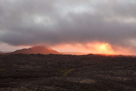 Beautiful sunset in empty lava field in Iceland. Deserted lava field covered with low clouds. Iceland misty midnight sun.