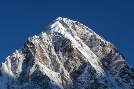 Pumori mountain peak on the famous Everest Base Camp trek in Himalayas, Nepal. Snowy mountain summit in the early morning with clear sky. Concept of success and goal achievement. Stock Photo