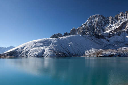 Beautiful Himalayan mountain range reflecting in ripples of Gokyo Lakes emerald green waters under the clear blue sky on a bright sunny day. Amazing mountain lake scenery.