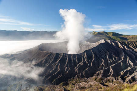 Bromo volcano crater at sunrise in morning mist from mt. Batok summit. Stock Photo