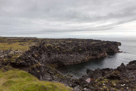 Melancholic Iceland landscape with dark cliff over Atlantic ocean and low gray clouds. Beautiful Iceland cliff landscape with green thick moss and gray clouds.