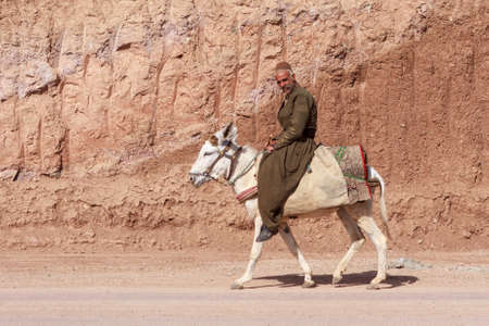 IRAN, KURDISTAN - MAY 19, 2012: Unidentified kurdish man riding donkey in Kurdistan.