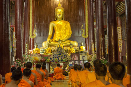 CHIANG MAI, THAILAND - NOVEMBER 04, 2014: Buddhist monks meditating in front of the Buddha image in Phan Tao Temple. Golden Buddha statue and buddhist monks praying.