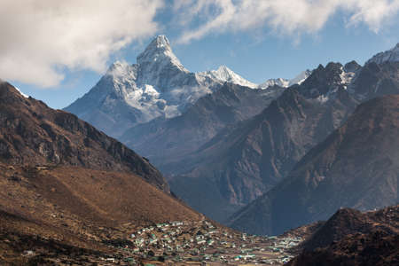 Ama Dablam mountain in Sagarmatha National Park, Himalayas, Nepal with mountain village beneath it. Nepali village in mountain valley on a bright sunny day. Beautiful mountain village landscape.