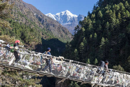 EVEREST BASE CAMP TREKNEPAL - OCTOBER 19, 2015: Suspension bridge over the gorge in Sagarmatha National Park in Himalayas. Trekkers walking over suspension bridge on their way to Everest base camp. Editorial