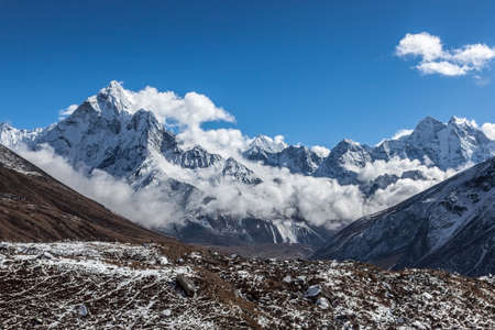 Beautiful panoramic mountain view of Ama Dablam summit on the famous Everest Base Camp trek in Himalayas, Nepal. Beautiful mountain landscape on a cloudy day. Grey clouds surrounding mountain summit.
