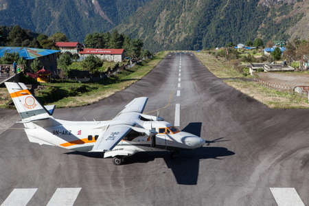 LUKLANEPAL - OCTOBER 18, 2015: Goma Air small airplane getting redy for take off from Tenzing-Hillary Airport in Lukla to Kathmandu. Remote Lukla airport runway between mountains.