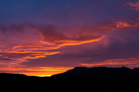 Amazing midnight sunset in Iceland with dark mountain silhouettes on the horizon. Bright colored clouds from orange to violet. Beautiful Icelandic landscape background.