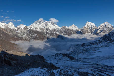 Mount Everest view from Renjo La pass. Picturesque mountain valley filled with curly clouds. Dramatic snowy peak of Everest rise above river of clouds. Sagarmatha National Park, Nepal, Himalayas.