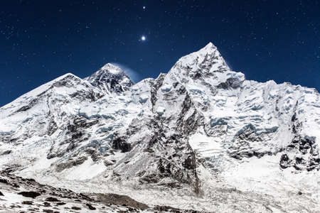 Everest mountain panoramic view on a starry night. Beautiful night mountain landscape under bright moonlight. Bright stars shining above mountain Everest peak. View from Kala Patthar, Nepal.