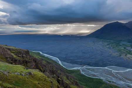 Aerial view of moraine glacier river in South Iceland. Dead black volcanic desert stretching to horizon. Heavy clouds and rain shower pouring far away. Stok Fotoğraf