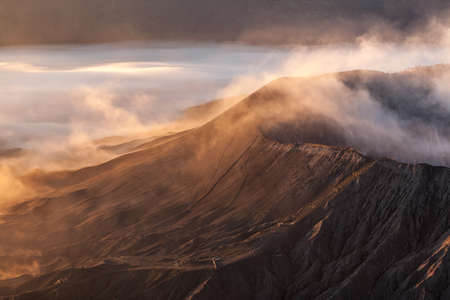 Bromo volcano infernal landscape. Stairway to hell concept. Unusual view down to smoking Bromo crater from Batok mountain on sunrise at Java island, Indonesia.
