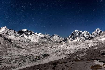 Panoramic view over Gorak Shep village on a starry night. Beautiful night mountain landscape under bright moonlight. Stars above Himalayan mountain village, view from Kala Patthar mountain.