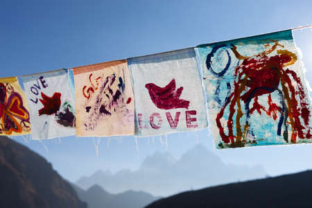 Childish painting of red pigeon hand drawn on white cloth. Hand painted flags waving on a bright sunny day. Love and peace concept expressed by children in Himalayan village of Thame, Nepal. 写真素材