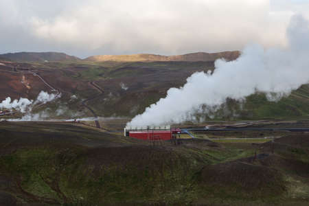 Krafla geothermal Power Station steaming. Myvatn volcanic area, Iceland, Europe. Steam coming out of pipes. Colorful, green and brown hills and mountains. Cloudy weather.
