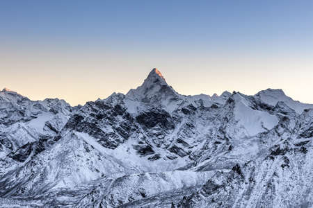 Beautiful Ama Dablam peak lit by the very first ray of morning sun. Alive photo.