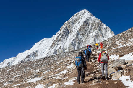 Group of trekkers coming up to Kala Patthar - the Everest mount view point - with Pumori peak on the background. Attractive photo. Stock Photo