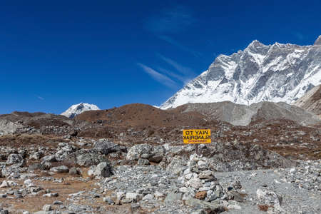Way to Island Peak sign installed on a rocky trail with Lhotse mountain on the background. Divine photo. Stock fotó