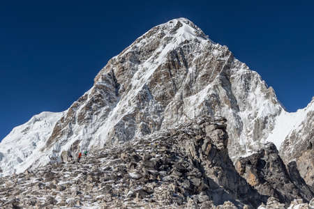 Trekkers coming up to Kala Patthar - the Everest mount view point - with Pumori mountain on the background. Astonishing photo. Stock Photo