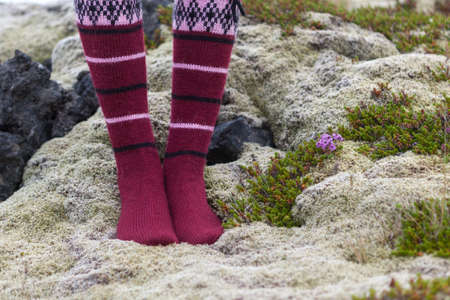 Girl wearing red Icelandic wool socks standing in the deep thick Icelandic moss and flowers. Fairisle traditional Icelandic woolen hand knitted socks with geometric pattern.