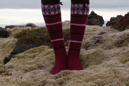 Girl wearing red Icelandic wool socks standing in the deep thick Icelandic moss among stones. Fairisle traditional Icelandic woolen hand knitted socks with geometric pattern. Reklamní fotografie