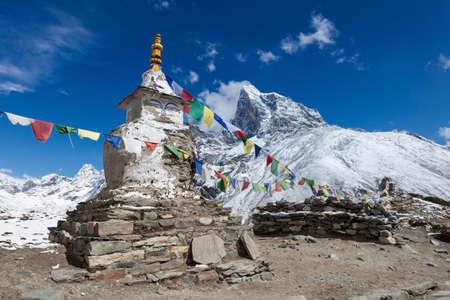 Buddyjskie flagi modlitewne na buddyjskim chorten na trasie Everest Base Camp w Himalajach w Nepalu.