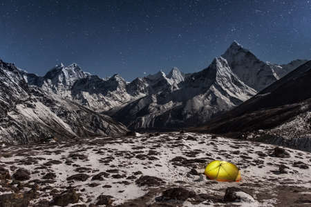 Concept of solitude and freedom in the wild. Night winter camping in the mountains. Grand photo.