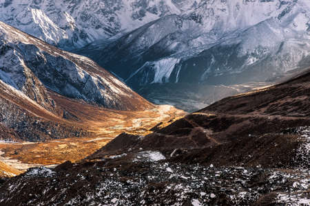 Abstract mountain background. Sunny valley among high snowy mountains on a bright sunny day. Himalayas mountains in Sagarmatha National Park, Nepal.. bold photo.